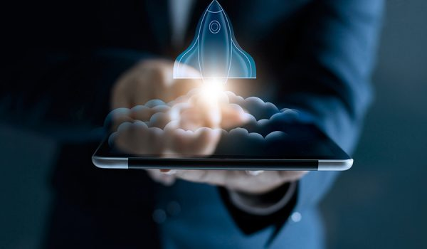 Startup concept, transparent rocket is launching and flying out of tablet on screen